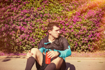 sportsman sitting in the park with bottle of water