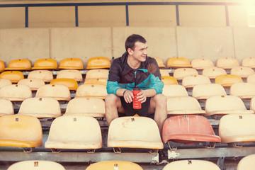 happy sportsman sitting on chair at stadium