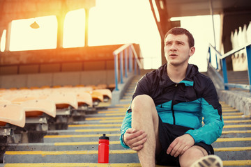 tired sportsman sitting on the stairs at stadium