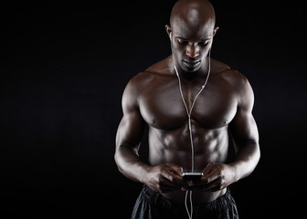 Muscular young man listening music on mobile phone