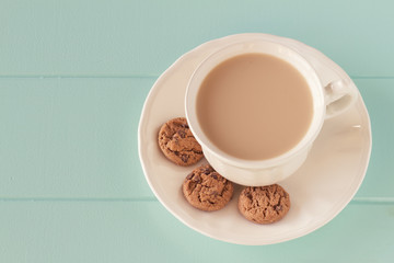 Coffee with milk and some chocolate chip cookies. Vintage style.