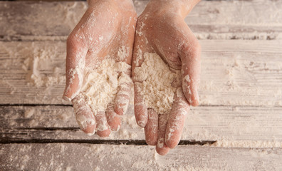 chef hands with flour over a wooden table