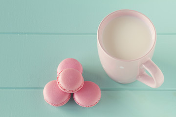 Some macarons (macaroon) and a pink mug with milk. Vintage