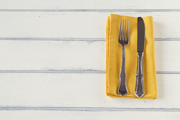 A  knife and a fork on a mustard napkin. Vintage style.