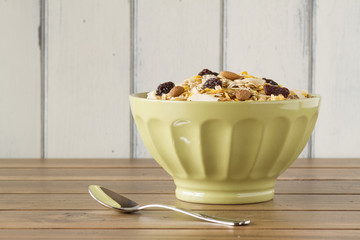 A green bowl with cereals and a spoon