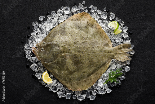 Poster Vis Fresh turbot fish on ice on a black stone table top view