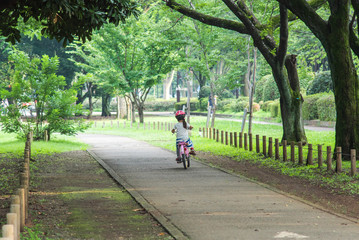 Asian girl training to ride a bicycle by herself