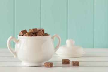 Brown cane sugar cubes in a sugar bowl. Vintage Style.