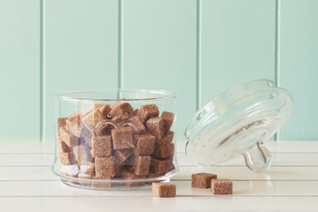 Some brown cane sugar cubes in a glass jar. Vintage Style.