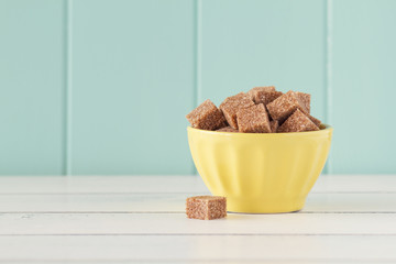 Some brown cane sugar cubes in a yellow bowl. Vintage Style.