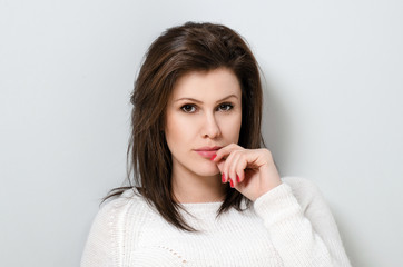Young woman in white sweater on the light background