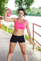 Sexy woman with pink kettlebell