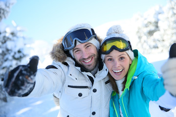 Cheerful couple of skiers showing thumbs up