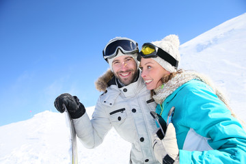 Cheerful couple of skiers ready to go down ski slope