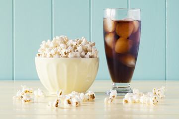 Pop corn in a bowl and a glass of cola