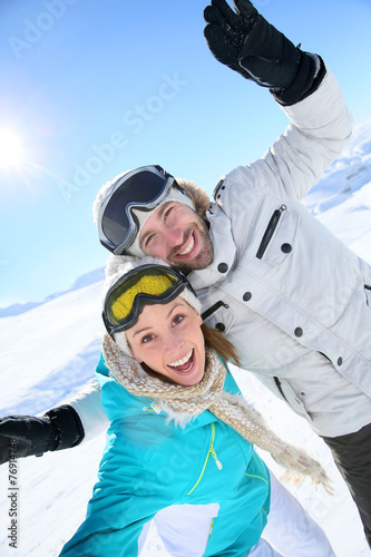 Poster Cheerful couple having fun at top of ski slope