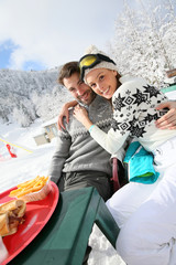 Couple of skiers having a snack on skiing day