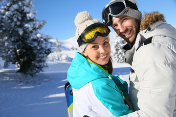 Cheerful couple standing in snowy mountain