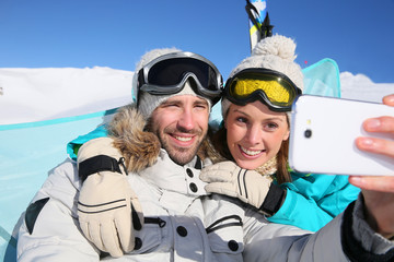Couple of skiers making selfy with smartphone