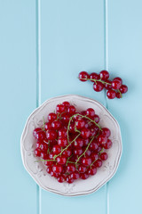 Red currants on a robin egg blue wooden table. Vintage Style.