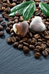coffee beans and chocolate candies on dark background, vertical