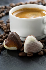 espresso, coffee beans and chocolate candies in a heart shape
