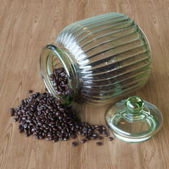 Coffee beans spilling out vintage glass jar on wooden surface