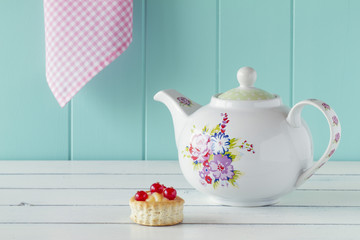 Teatime: a teapot and a vol-au-vent with red currants. Vintage.