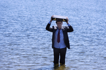 Businessman emerging from a reservoir to save your business
