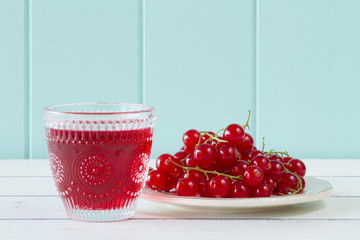 Red currants and juice on an white wooden table. Vintage Style.