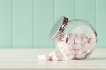 Marshmallows in a glass jar on a white wooden table. Vintage