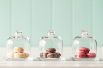 Some macarons (macaroon) in three glass bell jars.