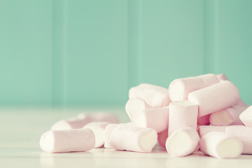A heap of marshmallows on a white wooden table. Vintage Style.