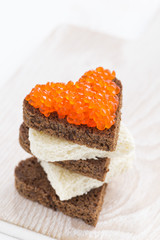 toast with red caviar in heart shape, vertical