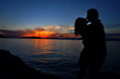 Silhouette of a couple kissing over sea sunset background