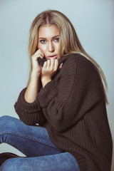 Pretty young woman sitting on floor wearing sweater