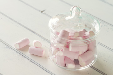 Some marshmallow in a glass jar on a white wooden table. Vintage