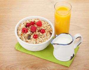 Healty breakfast with muesli, berries, milk and orange juice