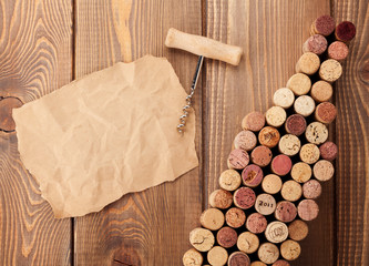 Wine bottle shaped corks, corkscrew and piece of paper