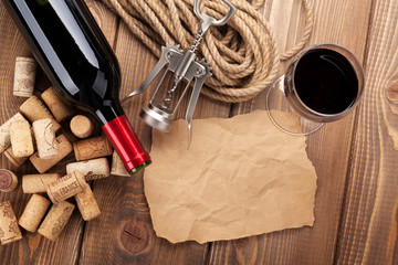 Red wine, corks, corkscrew and piece of paper