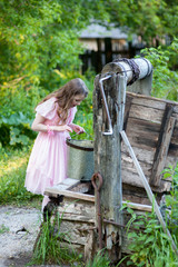 Little girl in a pink dress looks into the old well