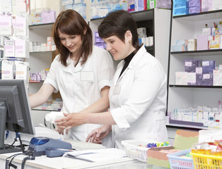 Two Friendly Pharmacists Working Together in the Drugstore .