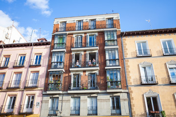 Young girls on balconies of a typical building facade on a stree