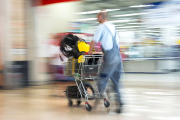 Worker in overalls pushing trolley in hardware shop