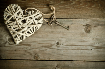 wicker heart handmade with the key lying on a wooden base