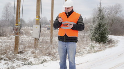 Electrical Engineer with  cell phone on the road in winter