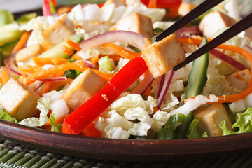Healthy salad tofu and vegetables with chopsticks macro