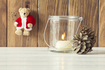 Christmas scene: a candle, pinecones and a bear with Santa dress