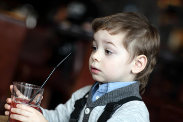 Portrail of thinking boy with red juice