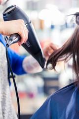 Friseur föhnt Frau die Haare im Friseursalon